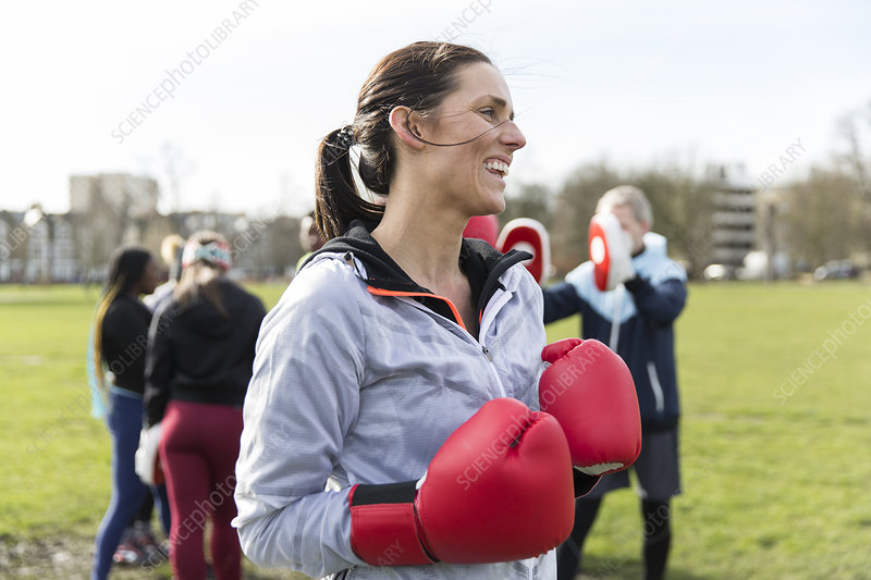 Smiling woman boxing in park