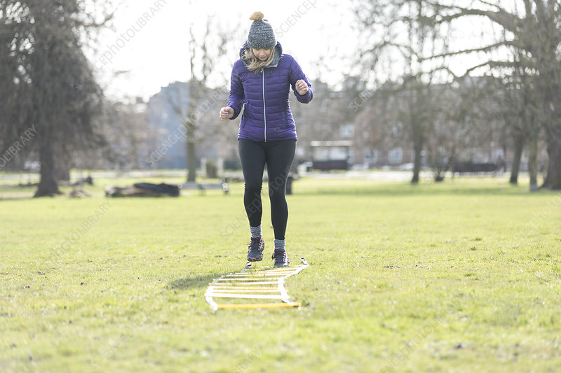 Woman doing speed ladder drill in sunny park
