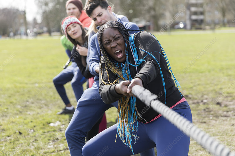 Determined team pulling rope in tug-of-war at park