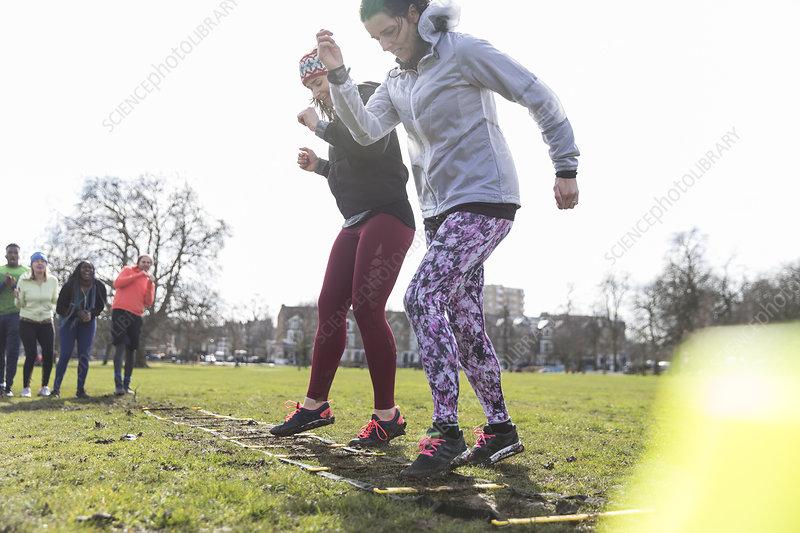 Women exercising, doing ladder drill in sunny park