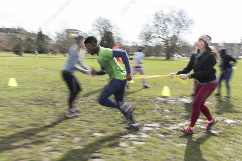 People racing, doing team building exercise in sunny park