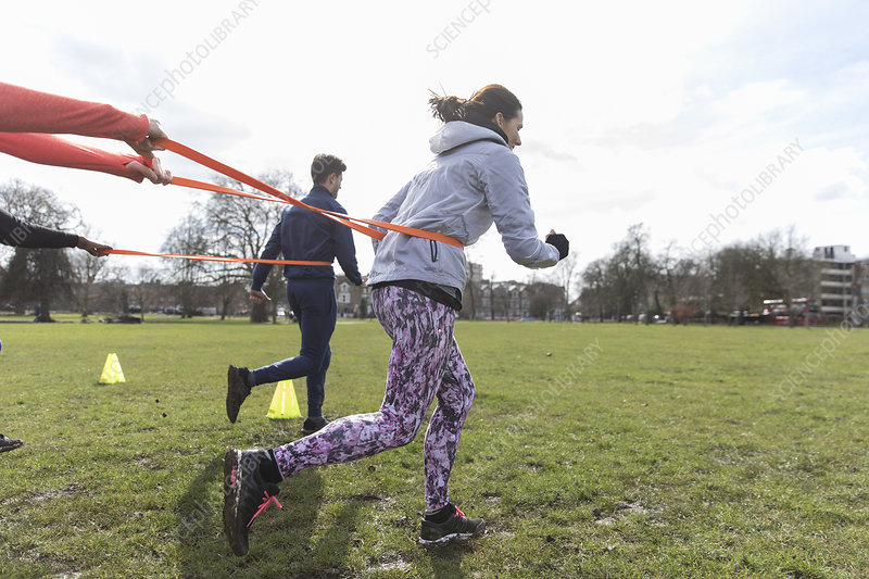 People doing resisted sprint exercise in sunny park