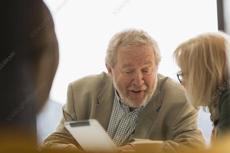 Senior business people using digital tablet in meeting