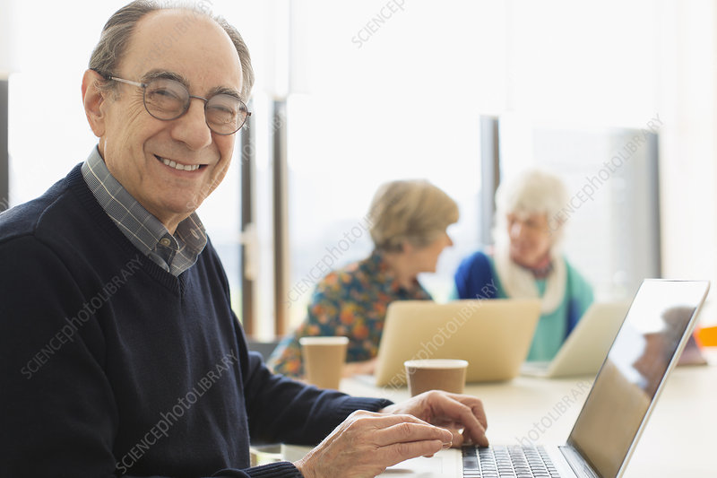 Portrait smiling senior businessman using laptop