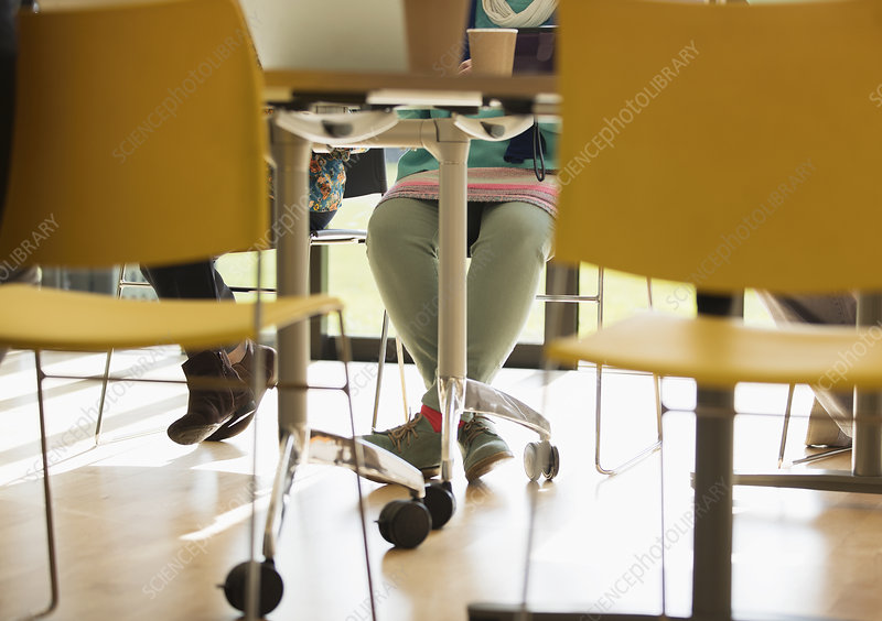 Legs of businesswoman under conference room table