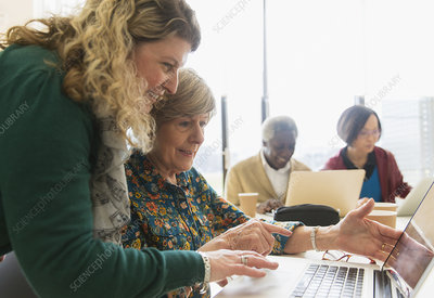 Businesswomen using laptop in conference room meeting