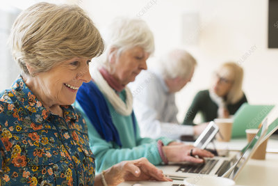 Senior women using laptops in conference room meeting