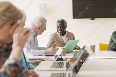 Senior businessmen using laptop in conference room meeting