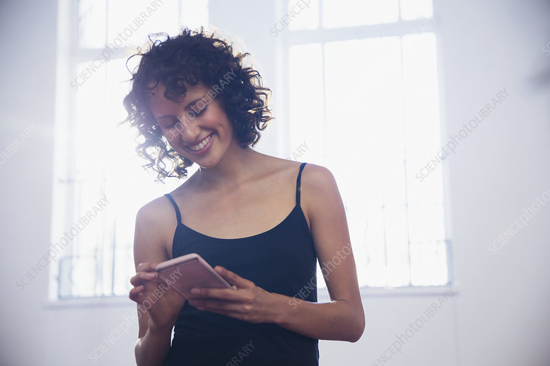 Smiling young female dancer texting with smart phone