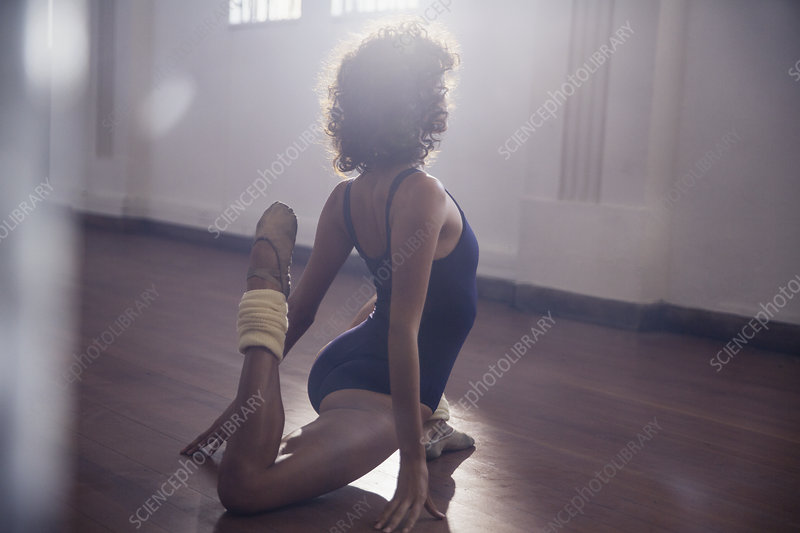 Young female dancer stretching