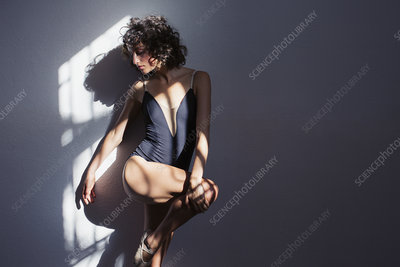 Female dancer stretching leg in sunlight at wall