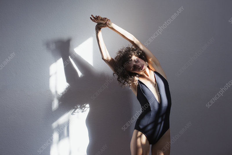Sensual young female dancer stretching in sunlight at wall