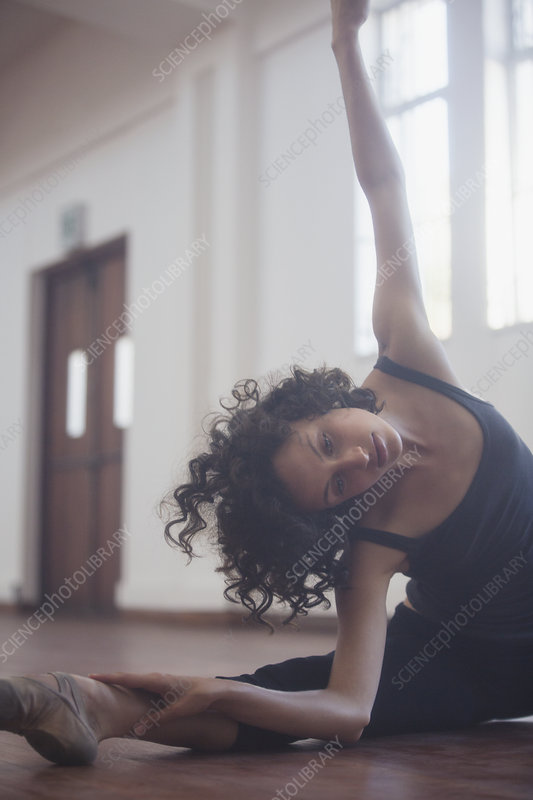 Graceful young female dancer stretching