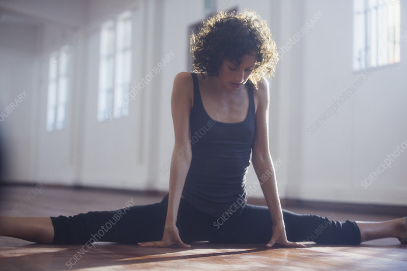 Strong young female dancer stretching, doing the splits