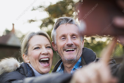 Happy, playful mature couple taking selfie