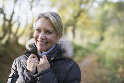 Portrait mature woman in parka in woods
