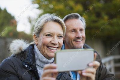 Happy mature couple using camera phone