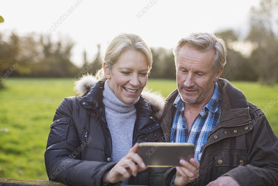 Mature couple taking selfie in park