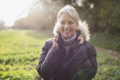 Portrait mature woman in parka in sunny park