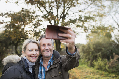 Happy mature couple taking selfie in autumn woods