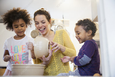 Playful mother and children baking in kitchen