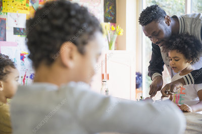 Father helping cut food for daughter at table