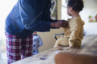 Father dressing baby son at dining table