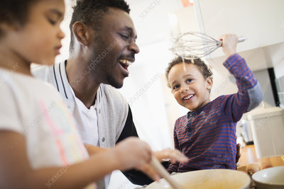 Playful father and sons baking in kitchen