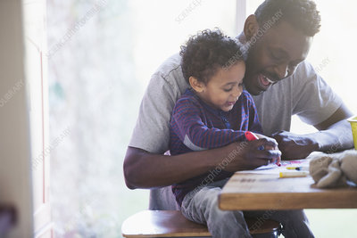 Happy father and toddler son colouring at table