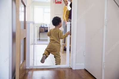 Cute baby boy balancing in doorway
