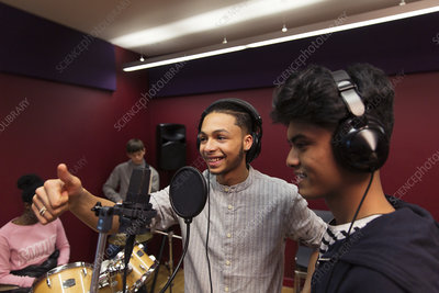 Smiling teenage musicians recording music