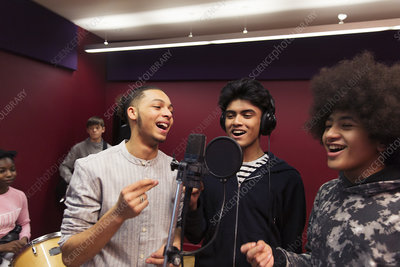 Smiling teenage boy musicians recording music