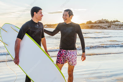 Happy male surfers on ocean beach