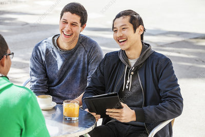 Male friends with digital tablet laughing