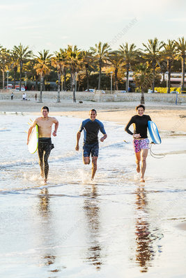 Enthusiastic male surfers running in surf