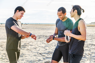Male runners checking smart watch fitness trackers