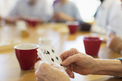 Close up senior woman playing cards with friends