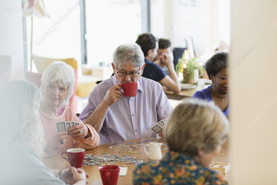 Senior friends playing games and drinking tea
