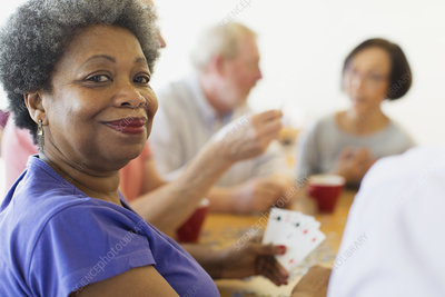 Portrait senior woman playing cards with friends