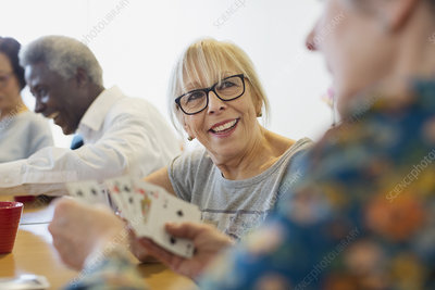 Smiling senior woman playing cards with friend