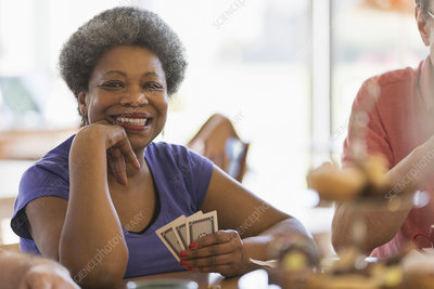 Portrait smiling, senior woman playing cards