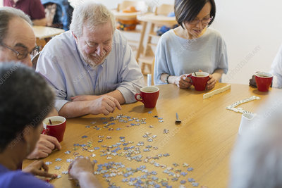 Senior friends assembling jigsaw puzzle