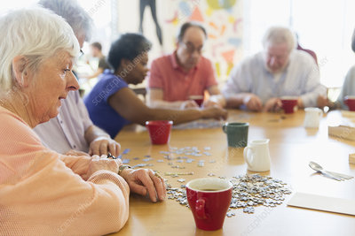 Senior woman assembling jigsaw puzzle with friends