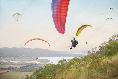 Paragliders in sky over landscape