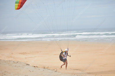 Male paraglider running on ocean beach