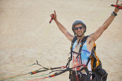 Portrait male paraglider strapped with equipment