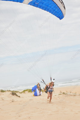 Female paraglider with parachute on ocean beach