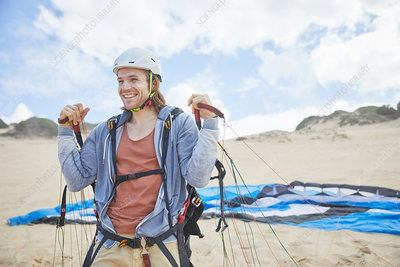 Smiling, paraglider with parachute on beach