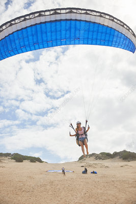 Female paraglider with parachute taking off