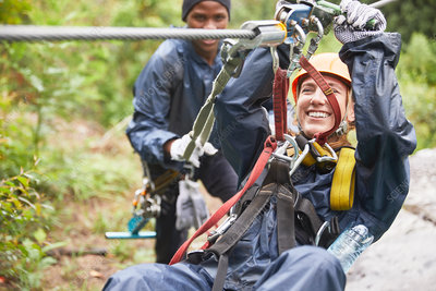 Smiling young woman zip lining
